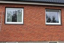 Fönsterbyte på tegelvilla. Nya PVC-fönster med svarta fönsterbleck för att matcha befintliga stilen på huset.